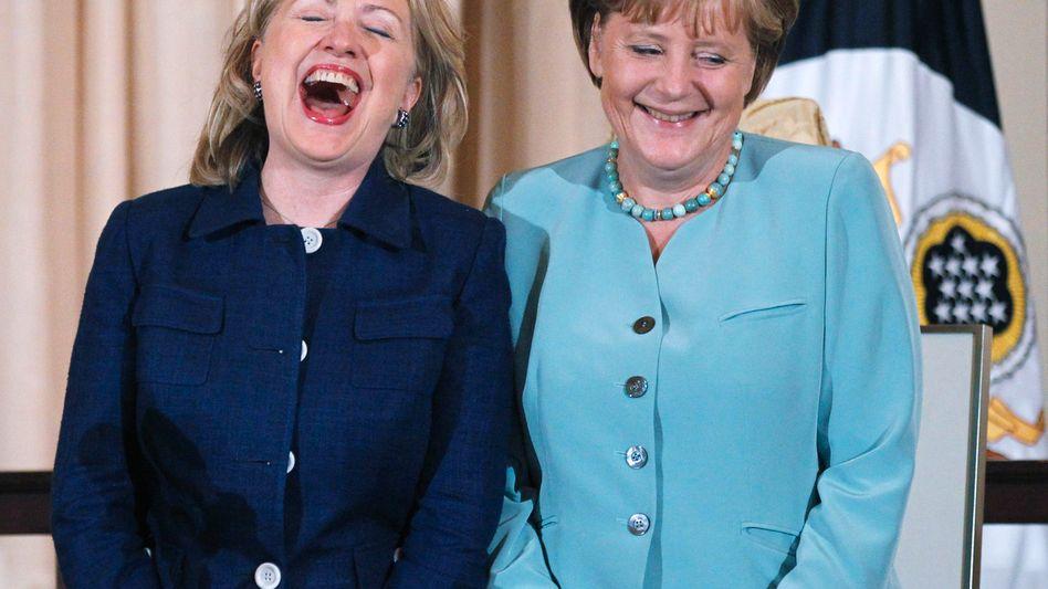 Grund zur Freude: Ob US-Außenministerin Hillary Clinton (l.) gerade die SPD-Glückwunschanzeige für Kanzlerin Angela Merkel gelesen hat?