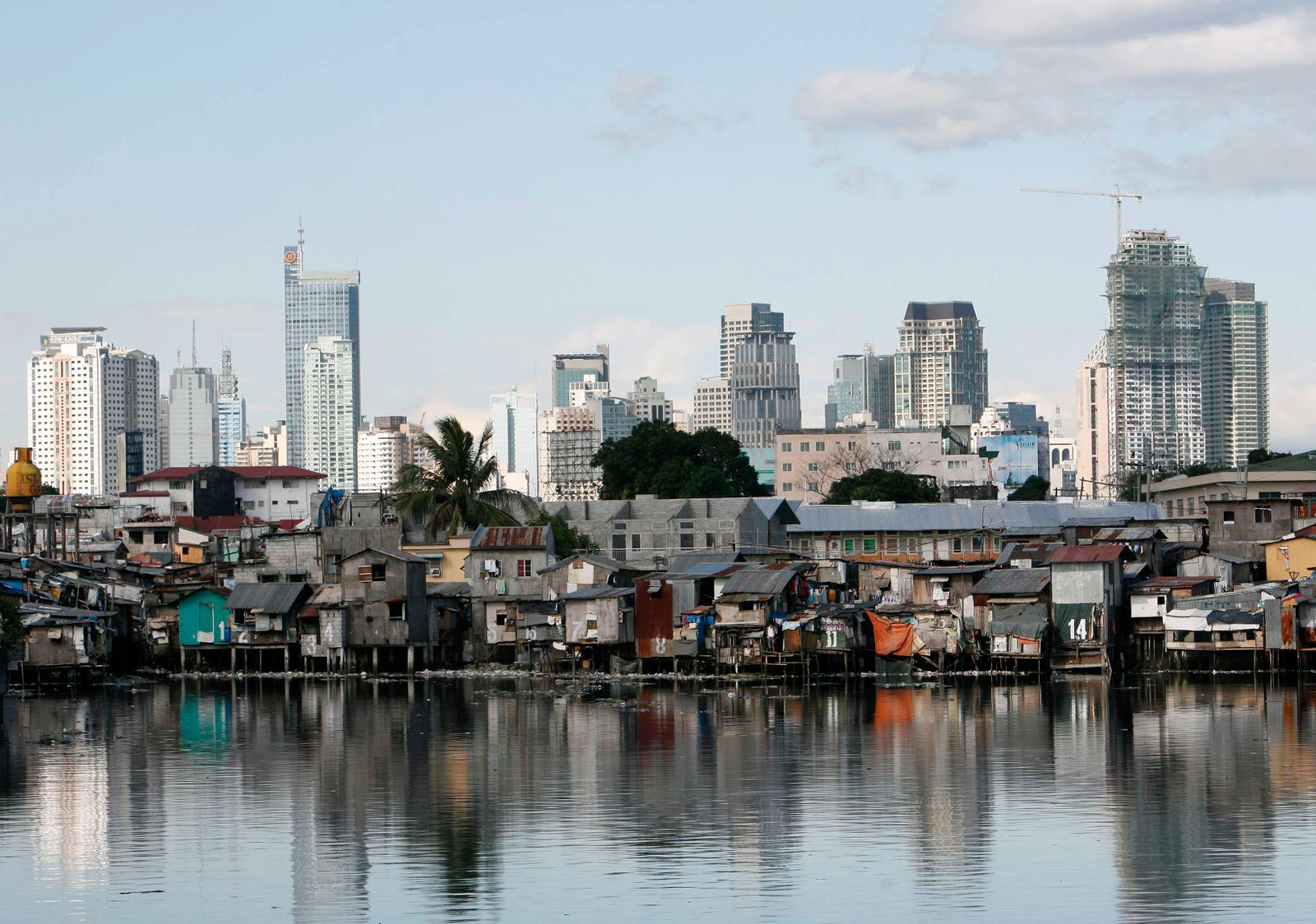 A shanty town is seen in front of the skyline of Manila's financial district of Makati City