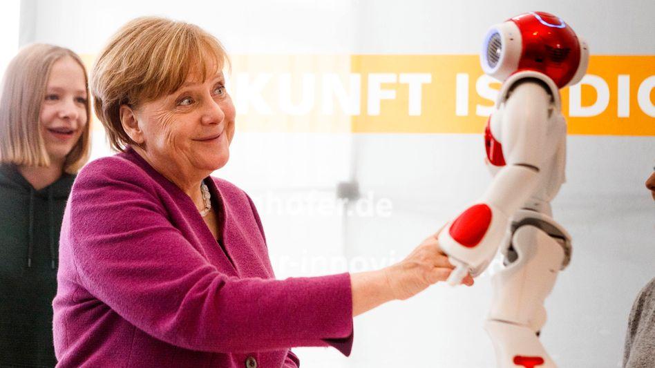 Hallo! Kanzlerin Angela Merkel mit einem Roboter des Fraunhofer Instituts.