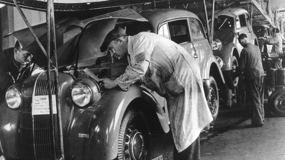 Arbeiter am Fließband bei der Endmontage des Kadett im Opelwerk in Rüsselsheim 1936.