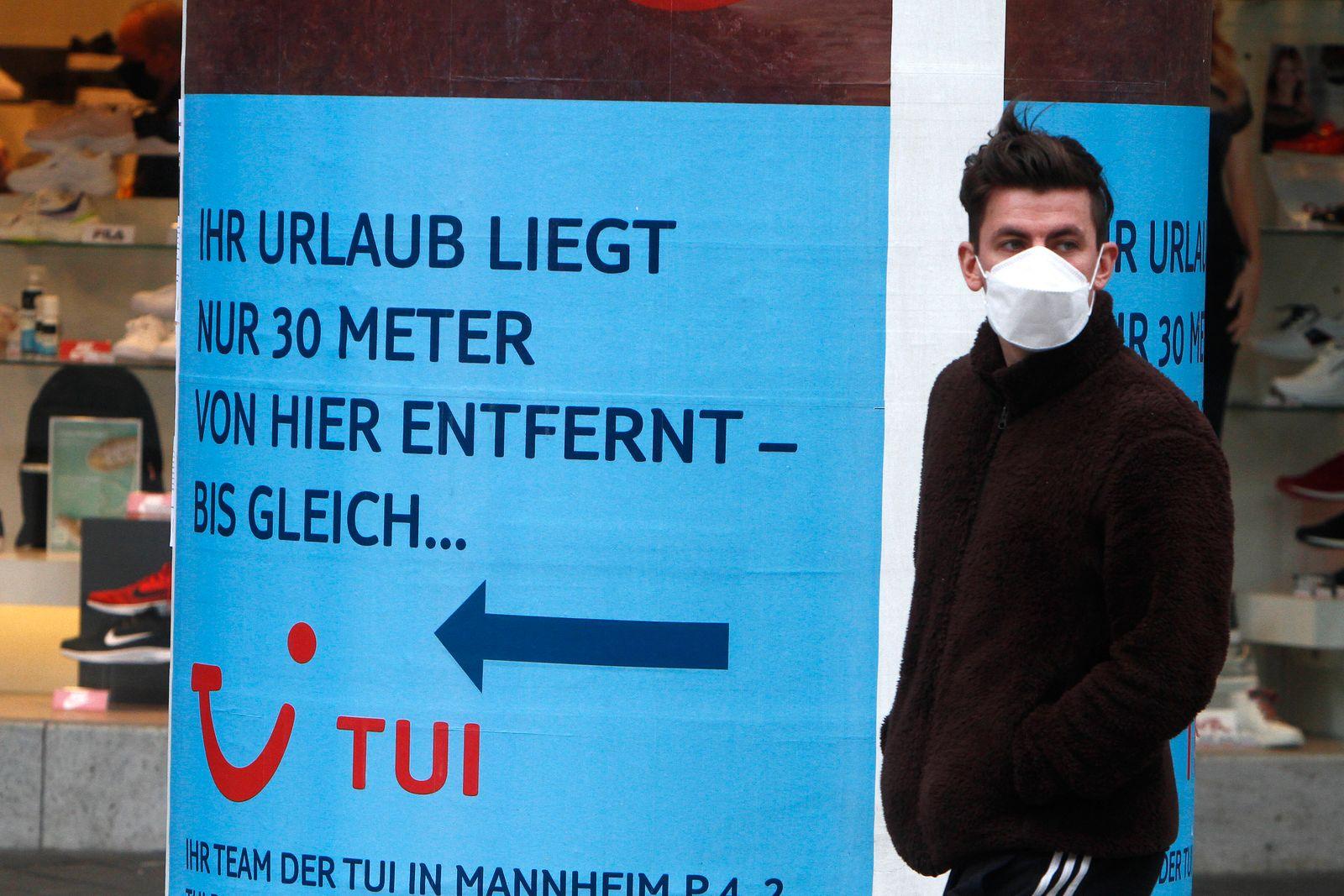 Mann mit Atemschutzmaske passiert ein Werbeplakat mit Aufschrift Ihr Urlaub liegt nur 30 Meter von hier entfernt - bis g