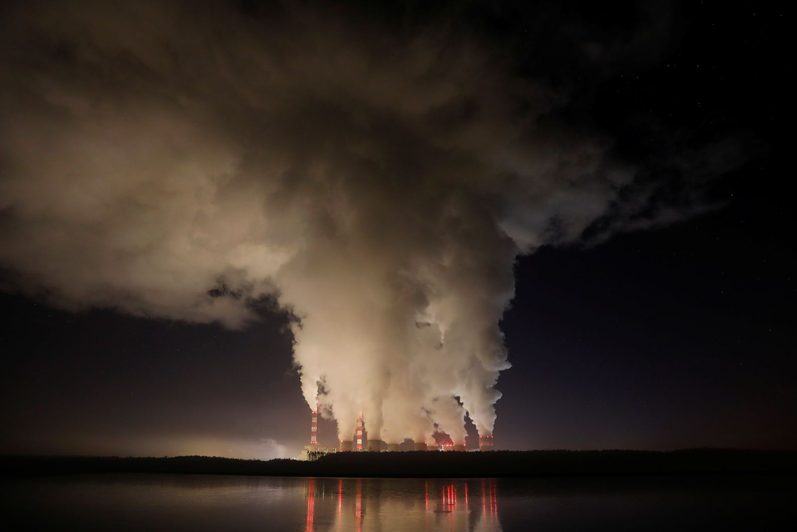 Smoke and steam billows from Belchatow Power Station, Europe's largest coal-fired power plant operated by PGE Group, at night near Belchatow,