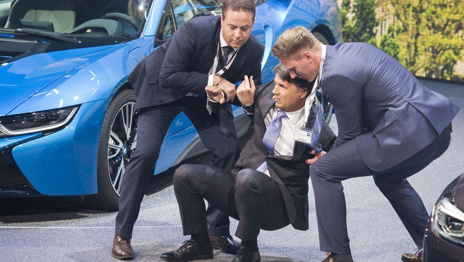 Schnelle Hilfe: BMW-Chef Harald Krüger nach seinem Zusammenbruch auf der IAA.
