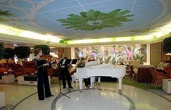 """Musiker auf der """"Queen Mary 2"""": Der Wintergarten wurde dem Konservatorium in Kew Garden bei London nachgebildet. An den Wänden ist ein riesiges Trompe d'oeil-Gemälde zu sehen"""