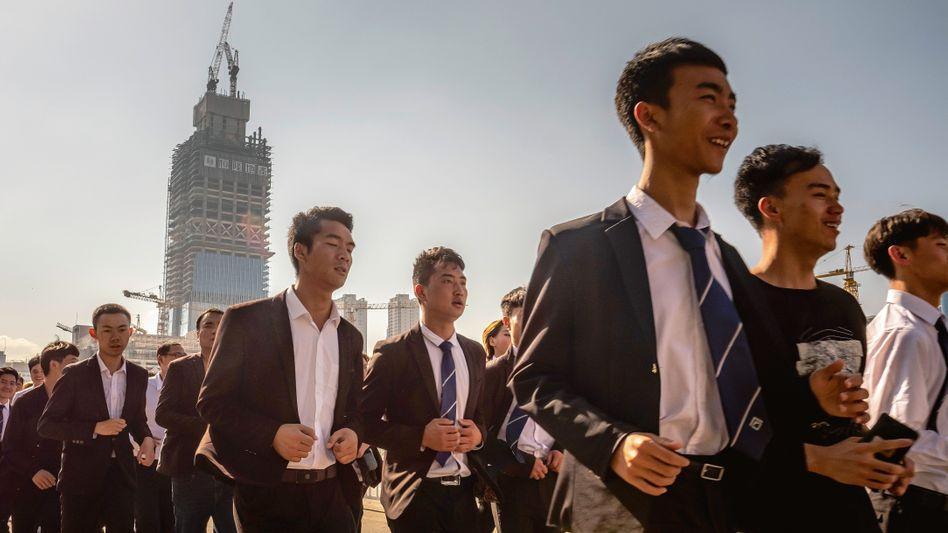 Schnell voran: Mitarbeiter einer Immobilienmaklerfirma beim morgendlichen Joggen im Stadtzentrum von Kunming im Süden Chinas