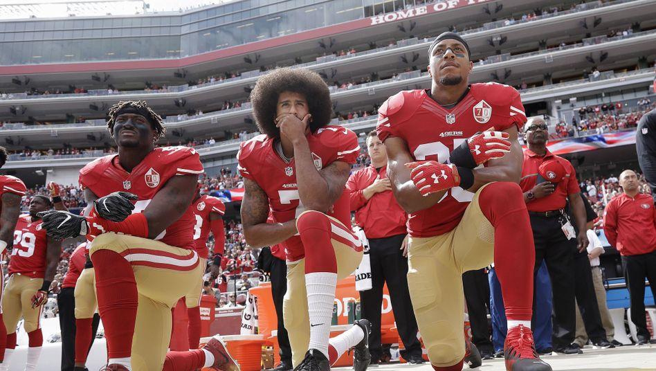 Kniender Protest: Im Oktober 2016 und auch später protestierten viele NFL-Spieler wie hier NFL-Superstar und Quarterback Colin Kaepernick (Mitte) gegen Polizeibrutalität und Rassimus in den USA