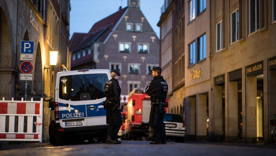 Polizisten stehen am frühen Morgen in einer Gasse vor einer Absperrung. Ein Mann war am 07.04. mit einem Kleintransporter vor einem Restaurant in eine Gruppe von Menschen gerast und hat zwei von ihnen getötet. Anschließend erschoss er sich nach Polizeiangaben in dem Wagen selbst. Bei dem Amokfahrer handelt es sich nach ersten Ermittlungen um einen 48 Jahre alten Deutschen. Einen terroristischen Hintergrund schloss die Polizei vorerst aus.