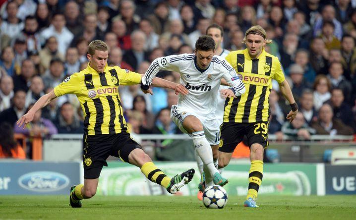 Zehn Millionen Facebook-Fans: Dortmunds Sven Bender (l.) und Marcel Schmelzer (r.) im Zweikampf mit Reals Star Mesut Özil.