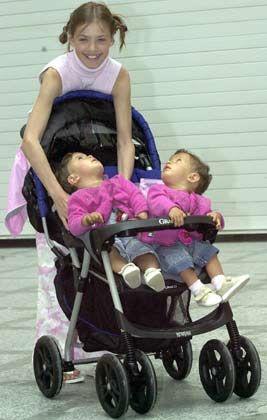 Tanita in rosa-weißer Jeans-Schlaghose mit rosafarbenem Rollkragenpollunder fährt das Zwillingspärchen Sophie und Julie im hochmodernen Kinderwagen mit dem klangvollen Namen Jogger Leisure Air Plus aus. Die Babylimousine für das neue Jahrtausend ist mit Flaschenhalterung und Monitor mit digitaler Anzeige für Temperatur, Uhrzeit, Geschwindigkeit, Entfernung und Kalorienzähler ausgestattet, für gesundheitsbewusste Eltern, die ihre Sprösslinge schon ganz früh an Fitness gewöhnen wollen.