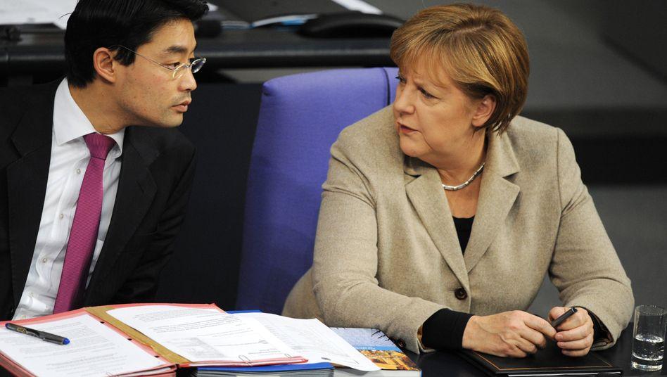 Böse Blicke: Bundeskanzlerin Merkel und Wirtschaftsminister Rösler sind beim Thema Finanztransaktionssteuer unterschiedlicher Meinung