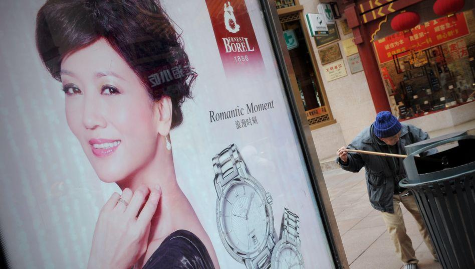 Plakat mit Luxuswerbung: Kein schöner Anblick für den Mann, der nach Resten im Müll sucht
