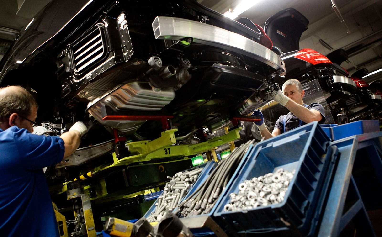Employees of German car manufacturer Mercedes Benz work on a Mercedes S-class limousine during a photo opportunity at the Mercedes plant in Sindelfingen near Stuttgart