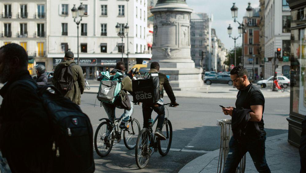"""Straßenkampf:Lieferkuriere in Paris. Sie werden von Anbietern wie Uber Eats oft nur pro Auslieferung bezahlt. Kritiker sprechen von """"moderner Sklaverei"""". Geld verdienen die Dienste dennoch nicht."""