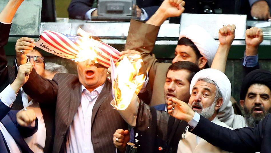 Als Protest gegen den Ausstieg der USA aus dem internationalen Atomabkommen verbrennen Abgeordnete im iranischen Parlament zwei Stücke Papier. Das eine zeigt die amerikanische Flagge, das andere soll eine symbolische Kopie des Atomabkommens sein.