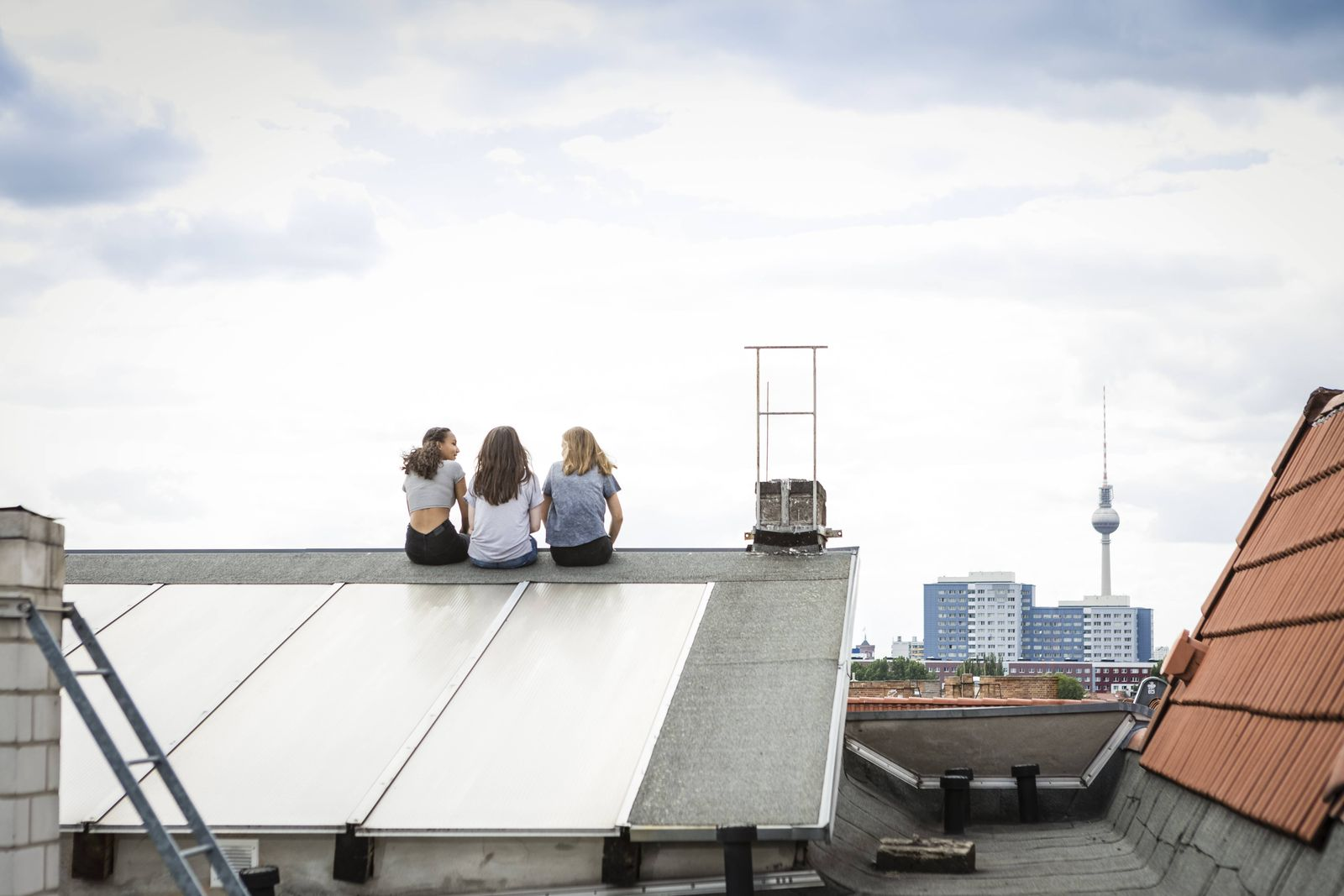 Germany Berlin back view of three friends sitting side by side on roof top model released Symbolfo