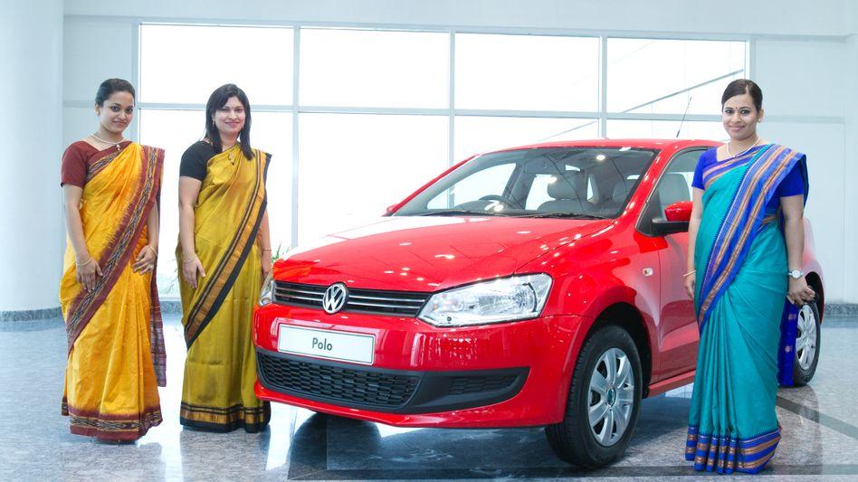 Inderinnen posieren neben einem VW-Polo im Volkswagen-Werk in Chakan bei Pune in Indien.