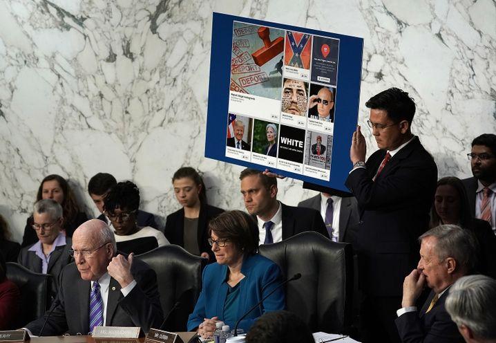 Patrick Leahy (links) lässt Plakate mit Hass-Posts und Fake-Accounts hochhalten
