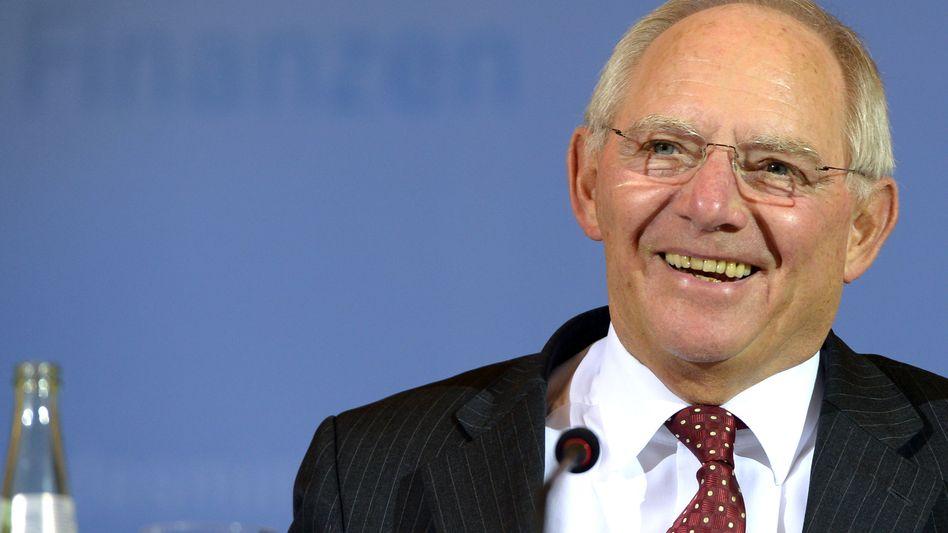 Da lacht er: Finanzminister Schäuble finanziert mit neuen Anleihen den rund eine Billion Euro hohen Schuldenberg des Bundes - und verdient damit derzeit sogar Geld. Für Sparer sind die Folgen der EZB-Geldpolitik dramatisch.
