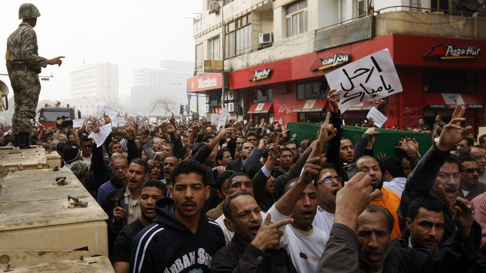 Ausnahmezustand: Ein Ägyptischer Soldat beobachtet seine Landsleute, während sie in Kairo gegen Präsident Husni Mubarak durch die Straßen ziehen