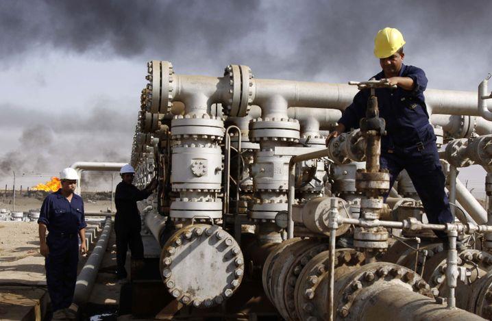 Doppelte Krise: Der Irak (hier Ölarbeiter in der Nähe von Basra) leidet unter niedrigen Ölpreisen sowie unter dem Krieg mit den IS-Milizen