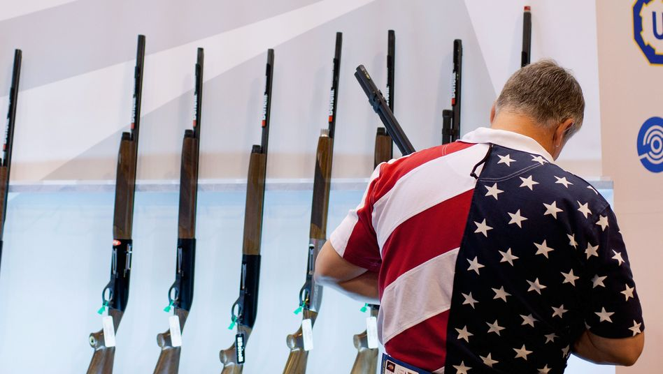 A man looks at the Benelli display of shotguns during the NRA Annual Meetings and Exhibits 2012 at the Americas Center in St. Louis, Missouri