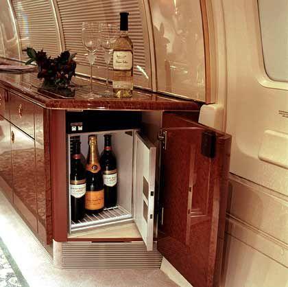 Eine Schranktür, die sich auch zum Spiegeln eignet: Weinkühler in der Kredenz eines Boeing Business Jet