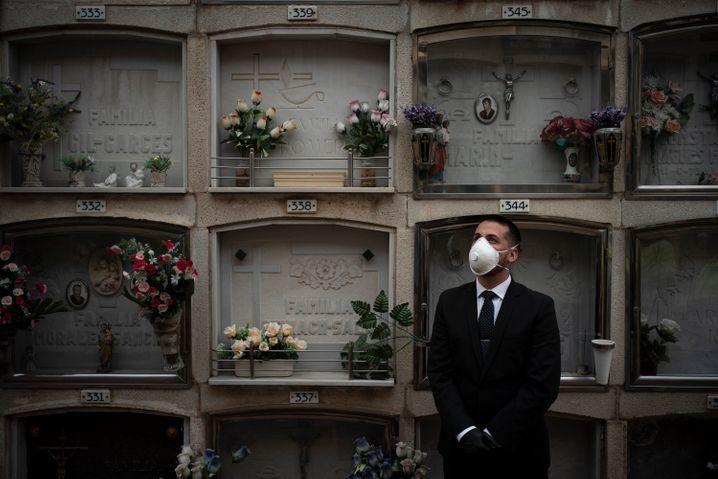 Mitarbeiter eines Bestattungsunternehmens auf einem Friedhof im spanischen Girona.