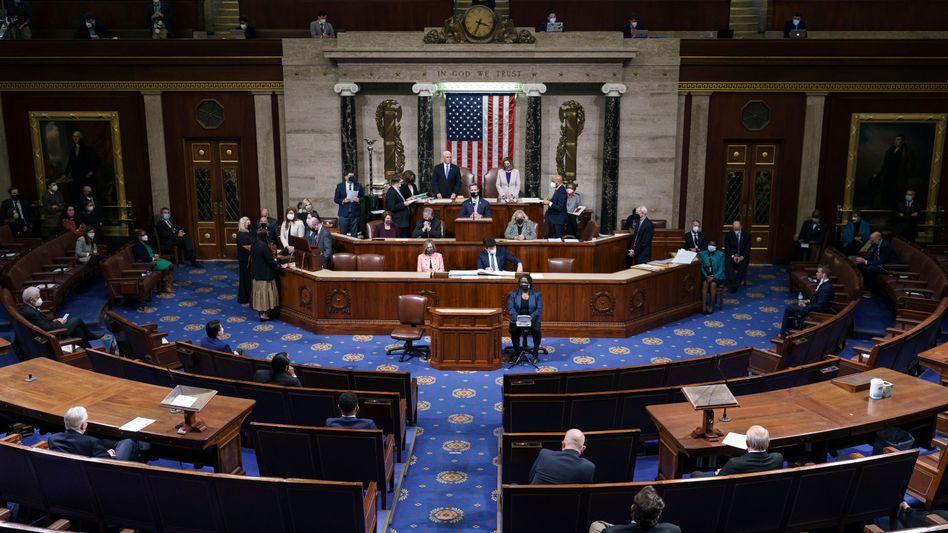 Ende Legende: Die Abgeordneten des US-Kongresses erheben sich am Donnerstagmorgen nach der Feststellung des Wahlergebnisses vom 4. November 2020 - Stunden zuvor hatten Anhänger des unterlegenen Präsidenten Donald Trump im Saal randaliert