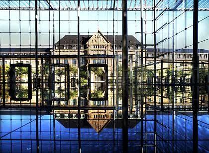 Spieglein, Spieglein in der Halle: Im gläsernen Bayer-Bau spiegelt sich die alte Unternehmenszentrale, so wird geschickt eine Verbindung zu der Geschichte des Konzerns aufgezeigt.
