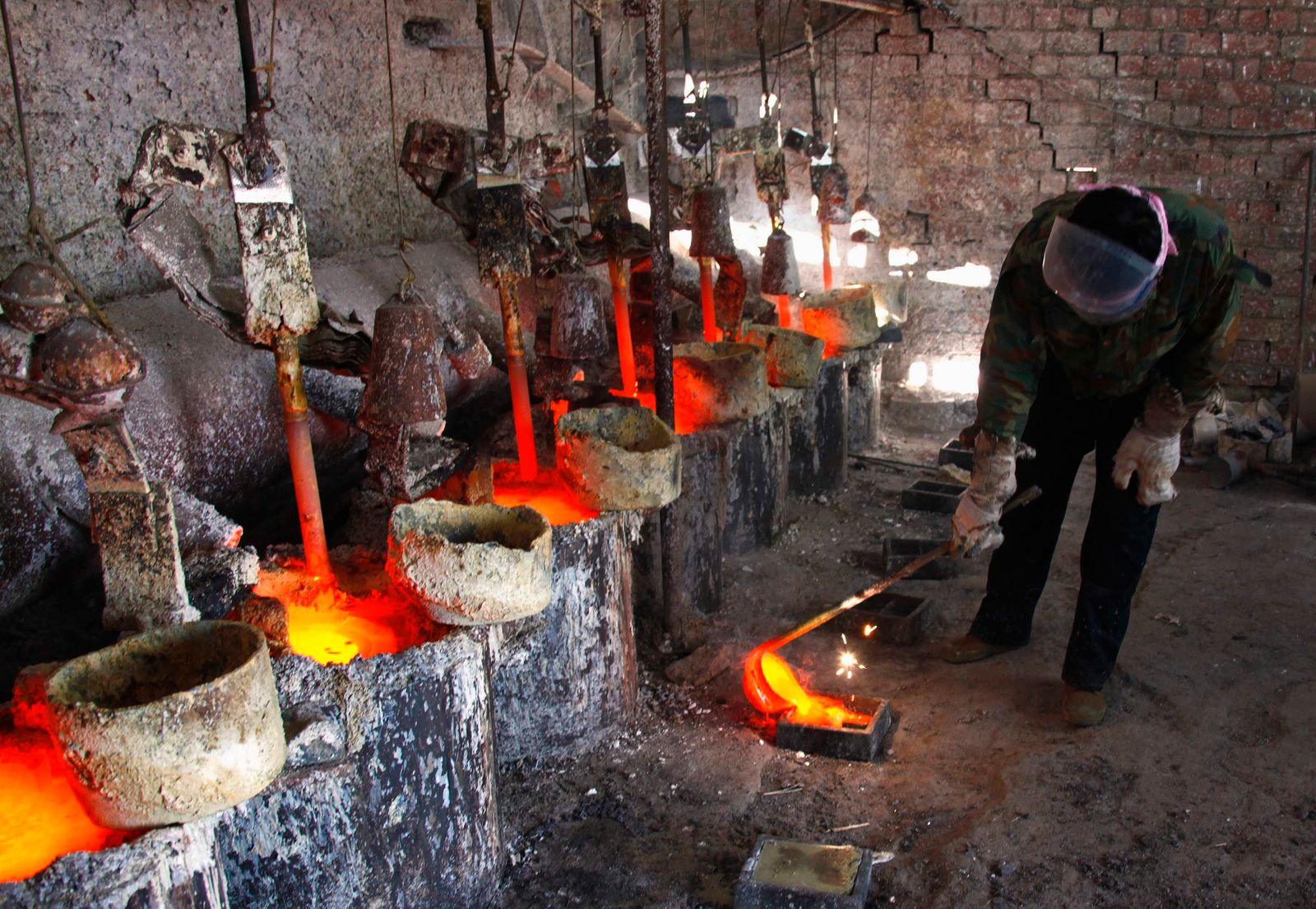 File photo of a worker at the Jinyuan Company's smelting workshop pouring the rare earth metal Lanthanum into a mould near the town of Damao