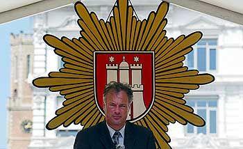 Innensenator Schill vor dem Polizeiemblem der Hansestadt: Der Sheriff und sein Stern