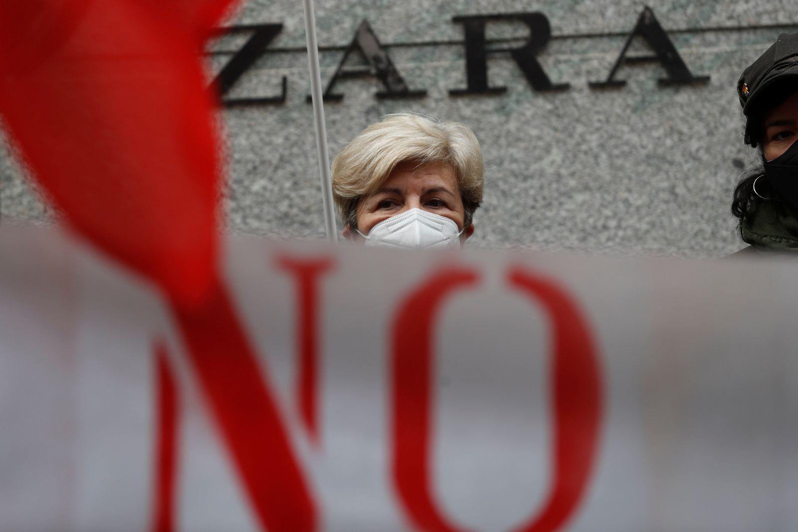 People protest outside a Zara clothing store in Madrid