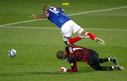 Thierry Henry (l.), David James: Nach einer verhängnisvollen, weil zu kurzen, Rückgabe eines englischen Verteidigers zu Torhüter James entscheidet sich dieser zu einer ruppigen Aktion, und riskiert einen Elfmeter. Den versenkt wenige Sekunden später Zinedine Zidane