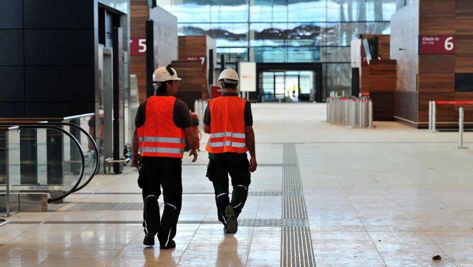 Machtlos gegen die Mängel: Arbeiter auf der Baustelle des Flughafens Berlin-Brandenburg Willy Brandt