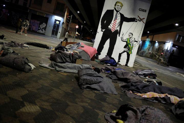 Obdachlose vor Anti-Bolsonaro-Graffito unter einer Brücke in Sao Paulo