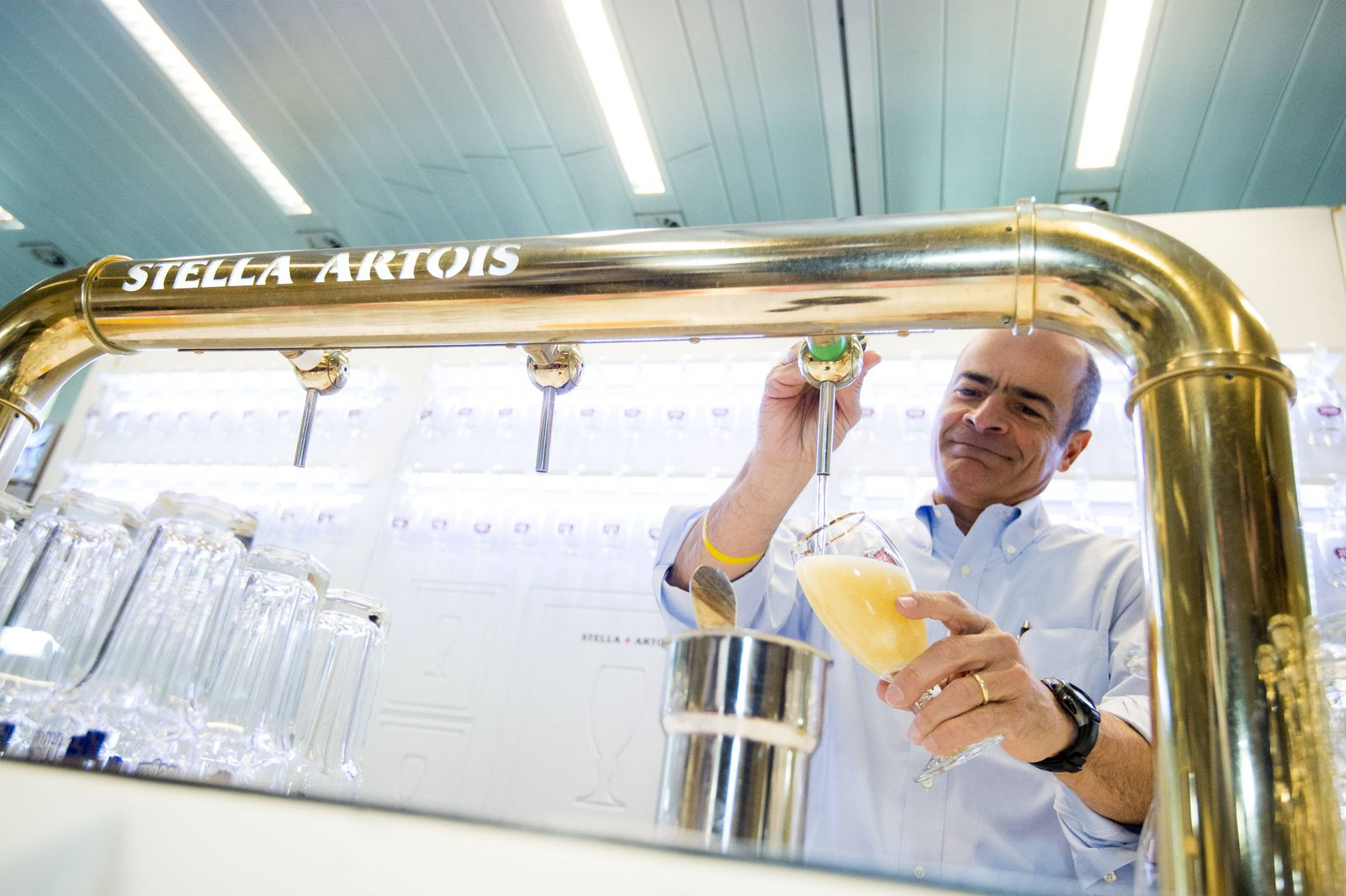 AB Inbev CEO Carlos Brito poses for the photographer tapping a Stella Artois beer at a press confere