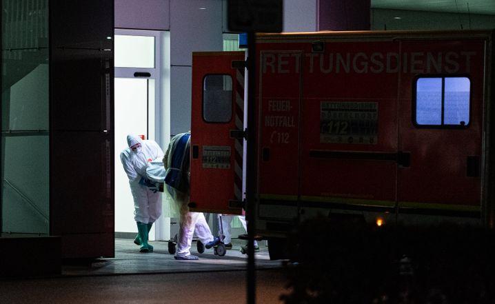 Mitarbeiter aus dem Leber- und Infektionszentrum des Universitätsklinikum in Düsseldorf nehmen den ersten mit dem Coronavirus Infizierten in Nordrheinwestfalen in Empfang