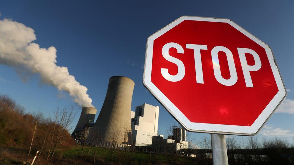 Stop-Schild vor einem Braunkohle-Kraftwerk von RWE