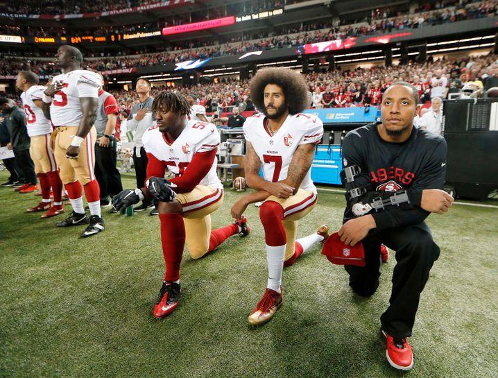 Colin Kaepernick (Mitte) setzte unter NFL-Spielern eine Protest-Bewegung gegen Polizeigewalt und Rassismus in Gang. Der Profi verlor seinen Job. Nike hat den Rebell zur Werbe-Ikone erhoben