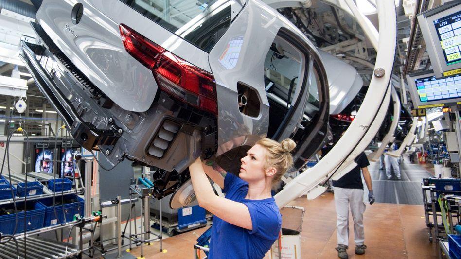 Produktion mit Einschränkung: Wegen der fehlenden Halbleiter müssen Autohersteller immer wieder ihre Produktion einstellen (im Bild eine Mitarbeiterin im VW-Werk Wolfsburg)