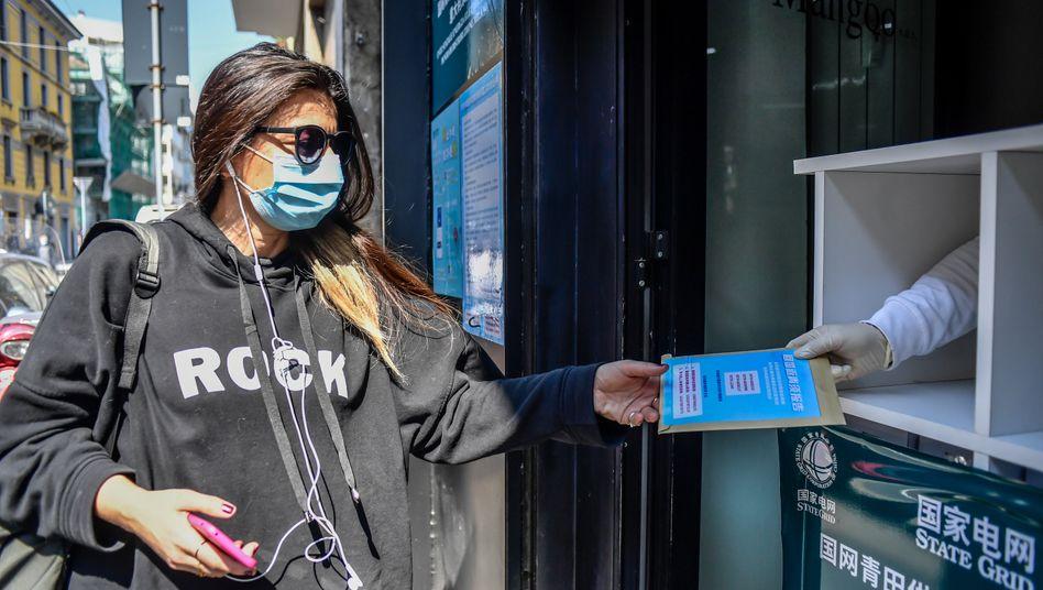 Mailand: Eine Frau holt sich eine kostenlose Packung mit zehn Mundschutzen in der Mailänder Chinatown ab.