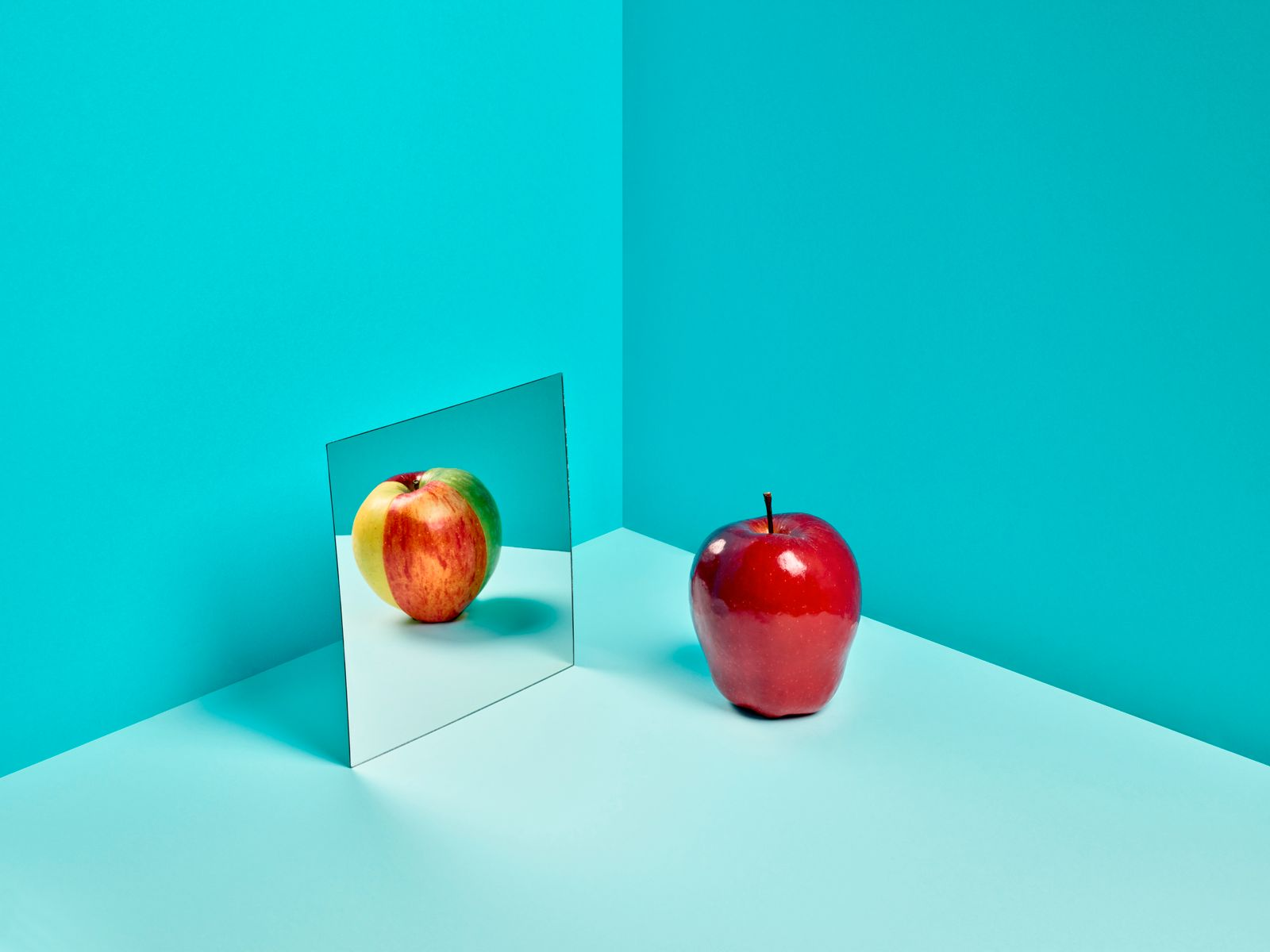 A Red Delicious apple in a mirror reflecting a mixed color apple made of slices of different varieties.