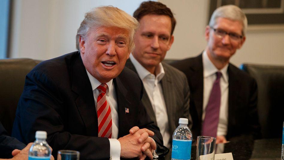 """Apple-Chef Tim Cook (rechts, neben Peter Thiel und Donald Trump): Geld in Irland """"lediglich bis zur Versteuerung in den USA aufbewahrt"""""""