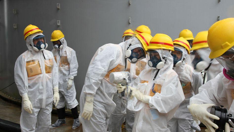 Prüfung kontaminierter Wassertanks in Fukushima: Japan hat die Folgen der größten Atomkatastrophe nach Tschernobyl noch längst nicht überstanden, die Regierung hat aber den Ausstieg aus dem Ausstieg der Kernenergie beschlossen