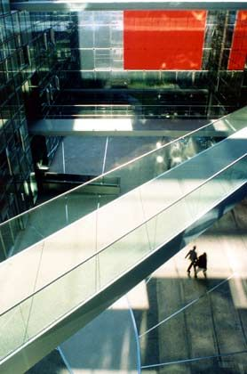 """HVB-Fazit von Hadi Teherani: """"Die Hochhaustürme hängen plakativ an Säulen, eine Variante zum BMW-Haus, die aber weniger überzeugt. Die filigrane Fassade lässt nicht unbedingt auf eine Bank schließen, insgesamt entwickelt sich der Baukörper zu einer Himmelsleiter. Viel wichtiger nehmen die Architekten den Innenraum, hier passiert sehr viel, was von außen gar nicht zu erwarten ist. Außen entsteht eher das Bild einer Forschungsstätte."""""""