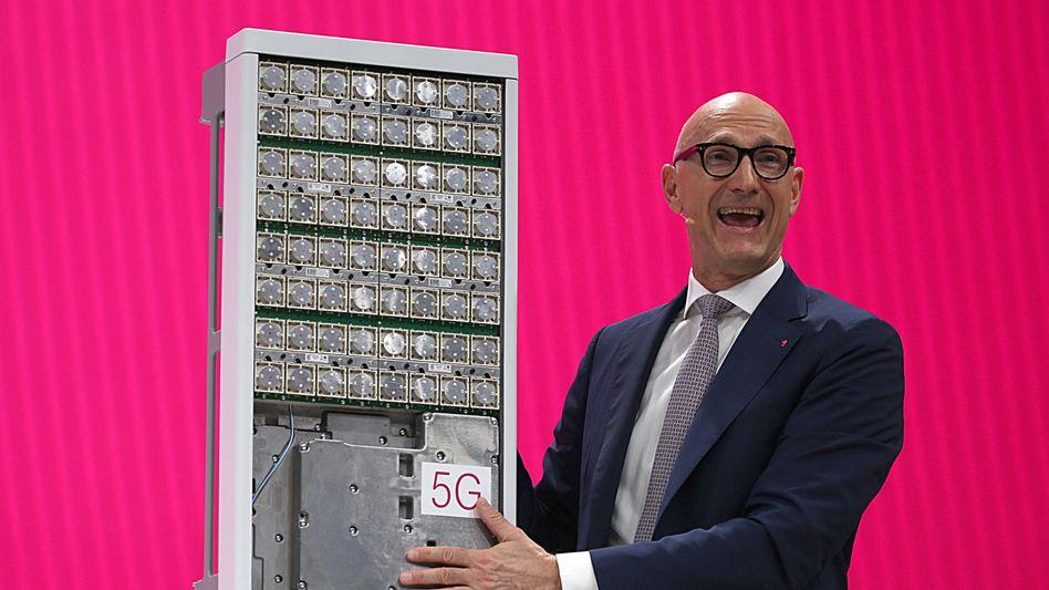 Timotheus Höttges, Chef der Deutschen Telekom, spricht neben einer 5G-Antenne zu Aktionären. In den Niederlanden hat jetzt die Tochter T-Mobile Frequenzen ersteigert
