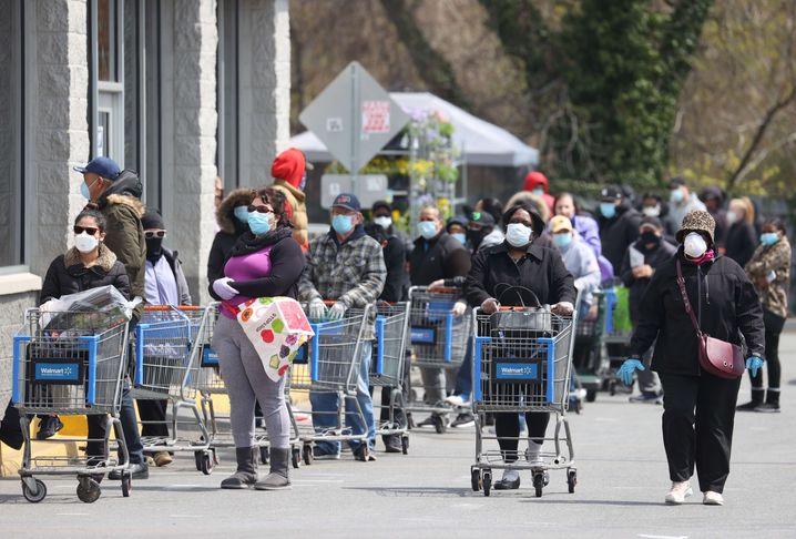 Lange Schlangen vor einem Walmart-Supermarkt in den USA: Der Konzern stellt täglich rund 5000 neue Mitarbeiter ein, um den Ansturm der Kunden und die hohe Nachfrage zu bewältigen.