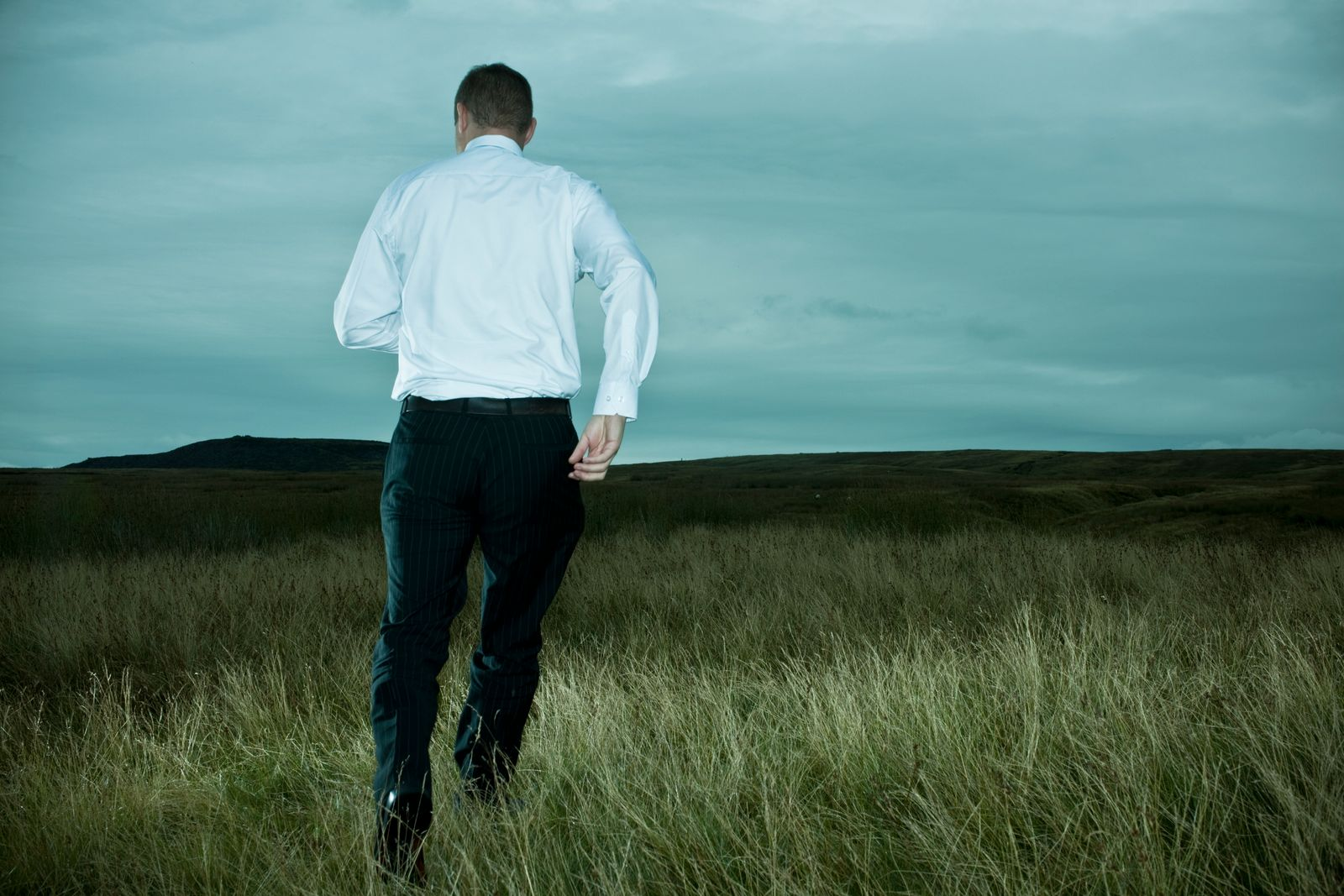 businessman running away on dark hillside