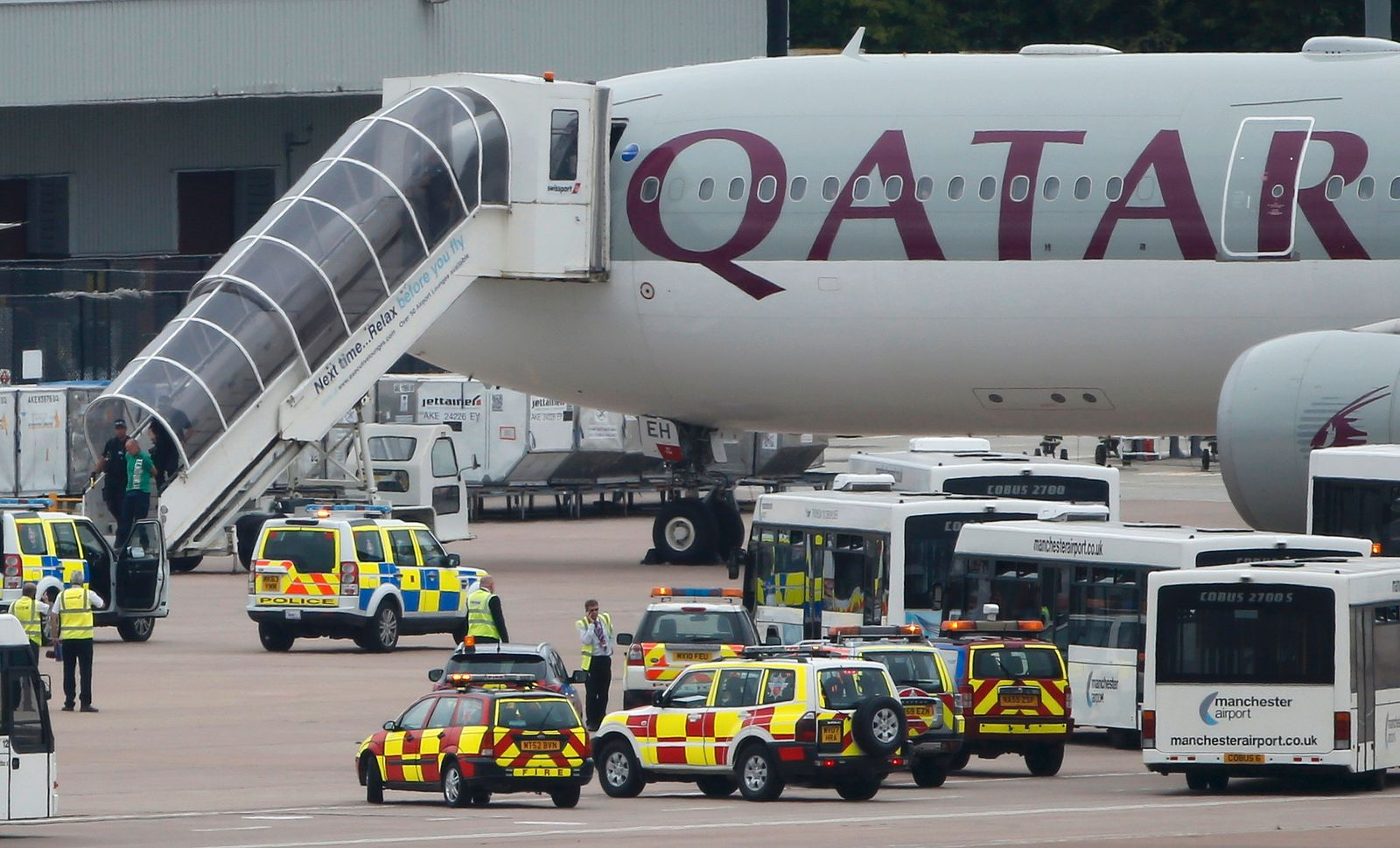 A man is escorted off a Qatar Airways aircraft by police at Manchester airport in Manchester, northern England