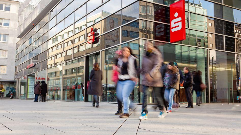 Menschen vor einer Sparkasse in Frankfurt: Immer mehr Kunden werden von Instituten in ganz Deutschland zur Kasse gebeten.